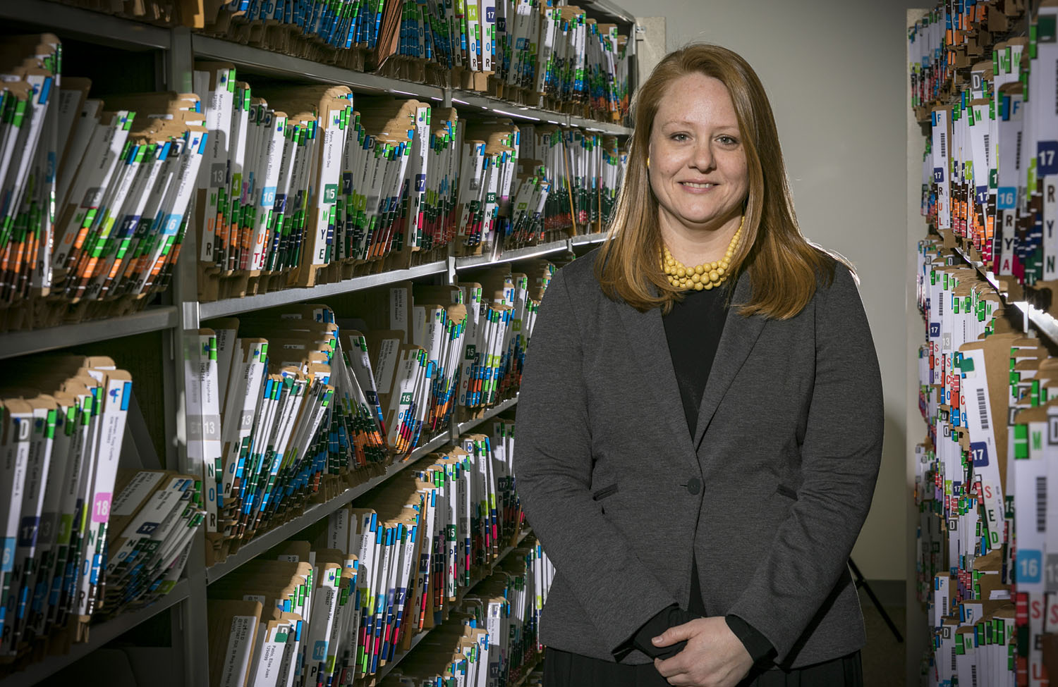 Sarah Buchanan, director of social services at the Knox County Public Defender's Community Law Office, poses among many shelves of file folders