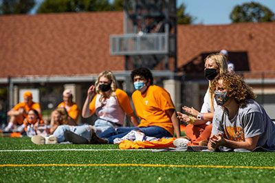 Students lounging on practice field in masks