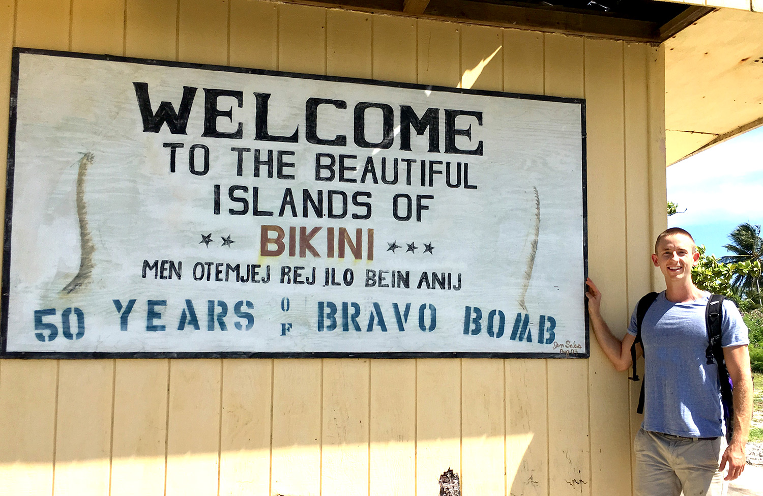 Adam Stratz poses in front of a sign welcoming visitors to Bikini Atoll, site of the largest nuclear explosion the U.S has ever conducted.