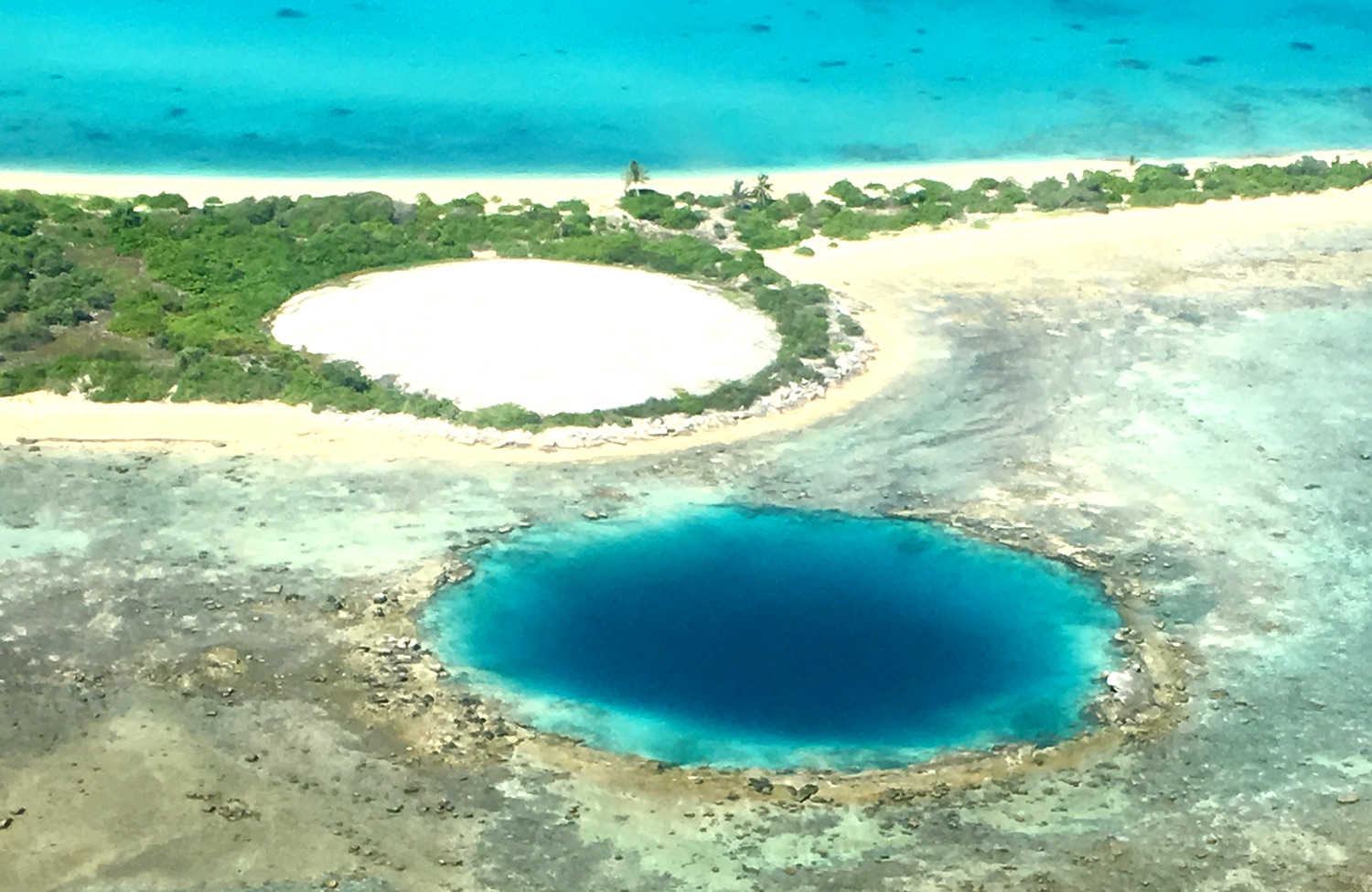 A pair of twin blast craters from the Cactus, left, and Lacrosse nuclear weapons tests on Enewetak Atoll are visible from the air. The Cactus crater was filled with debris and capped with concrete.
