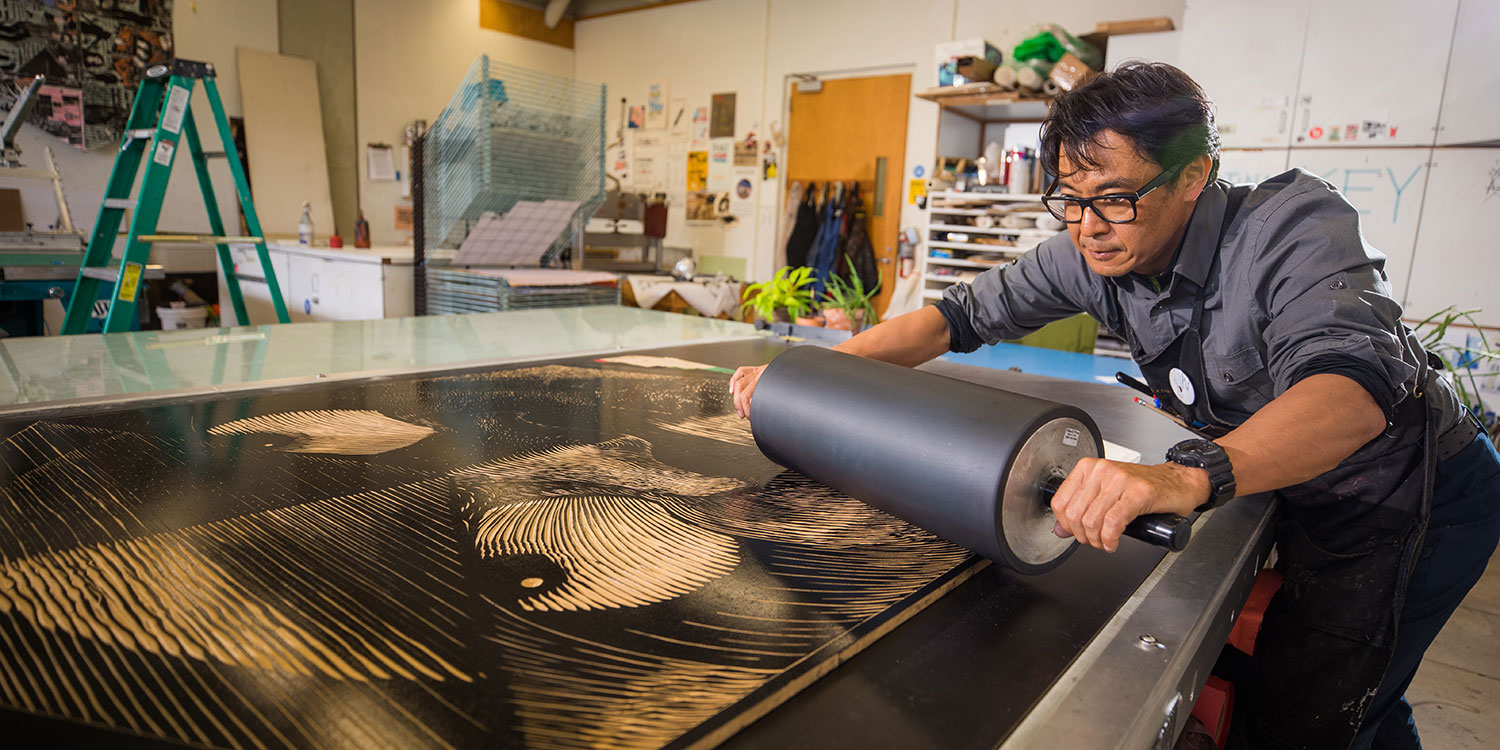 Associate Professor Koichi Yamamoto rolls ink on a woodcut for one of his kite prints